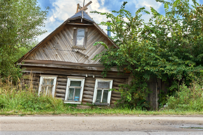 Old rickety crumbling abandoned house in a small russian town standing near a road