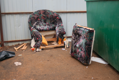 Old broken armchair with torn upholstery thrown into the dustbin